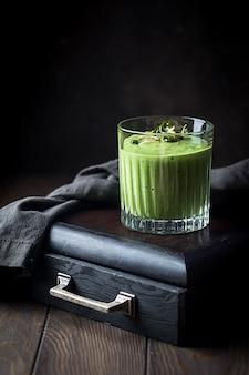 Zielone wegańskie smoothie ze szpinakiem i kiełkami na ciemnej drewnianej powierzchni.