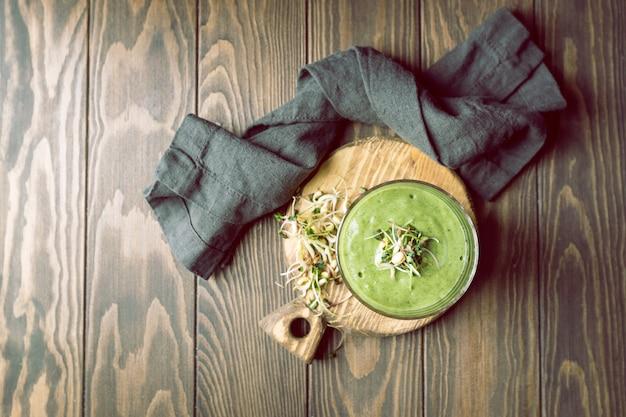 Zielone wegańskie smoothie ze szpinakiem i kiełkami na ciemnym drewnianym blacie