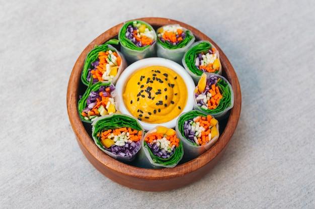 Zielone wegetariańskie sajgonki w misce wokół sosu curry.