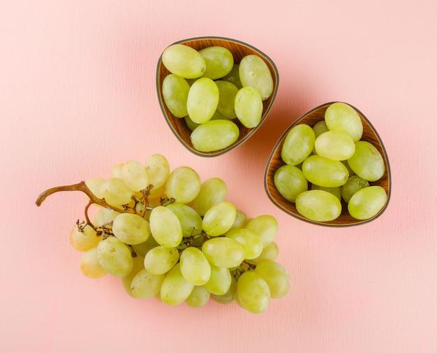 Zielone winogrona w miseczkach na różowo.