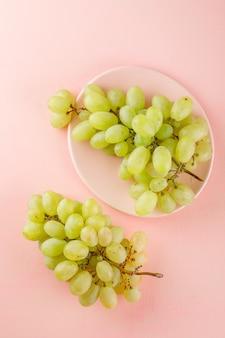 Zielone winogrona w talerzu na różowo.