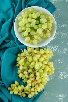 Zielone winogrona w talerzu na tynku i tekstyliach
