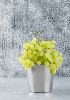 Zielone winogrona w widoku z boku mini wiadra na tynku i nieczysty szary