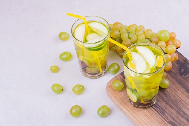 Zielone winogrona z dwiema szklankami soku na drewnianej desce