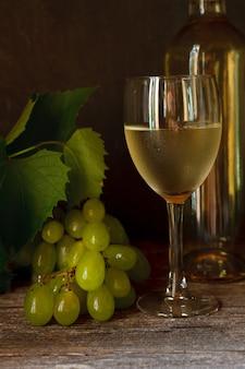 Zielone winogrona z liśćmi, szkło, butelka białego wina