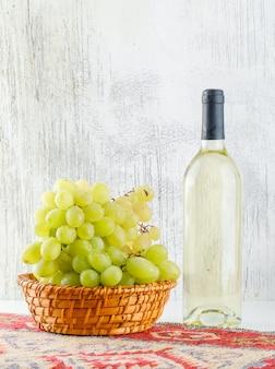 Zielone winogrona z winem, kilimowy dywanik w koszu na białym i nieczysty,