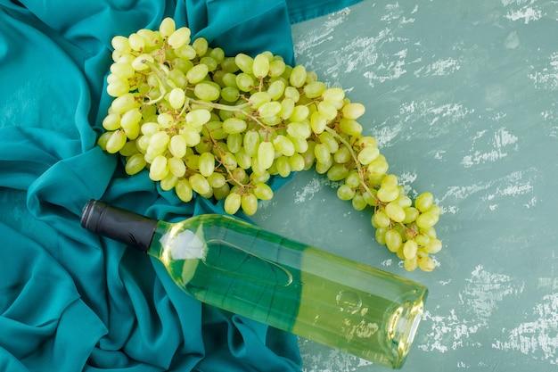 Zielone winogrona z winem leżały płasko na tynku i tkaninie