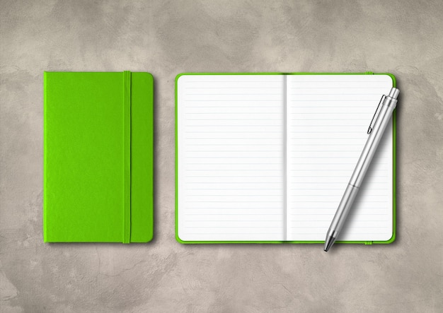 Zielone, zamknięte i otwarte zeszyty w linie z długopisem. na białym tle na betonowym tle