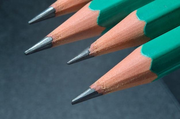 Zielone zaostrzone drewniane ołówki z czarnym ołowiem na ciemnym teksturowanym tle. zbliżenie.