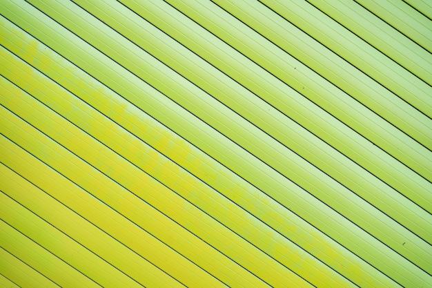Zielone żelazne blaszane ogrodzenie pokryte tłem. metalowa tekstura