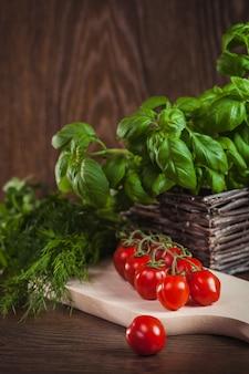 Zielone zioła i gałązka pomidorów cherry na drewnie