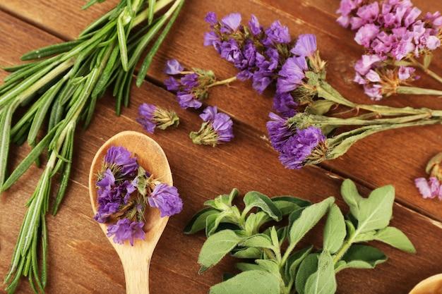 Zielone zioła i liście na drewnianym stole, zbliżenie