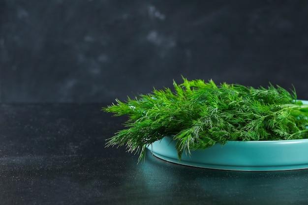 Zielone zioła kulinarne koperku w niebieskim naczyniu