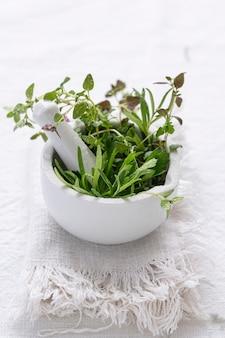 Zielone zioła w moździerzu w fotografii żywności