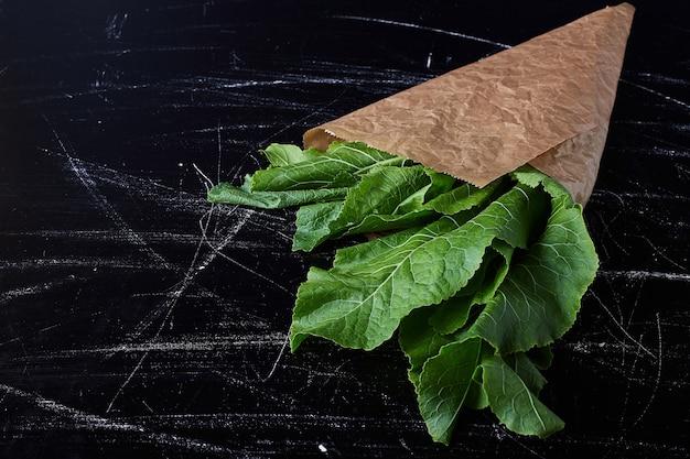 Zielone zioła w papierowym opakowaniu.
