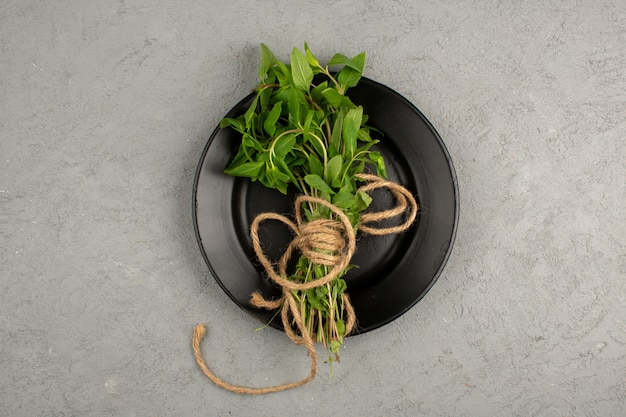 Zielone zioła w środku czarny talerz na szaro