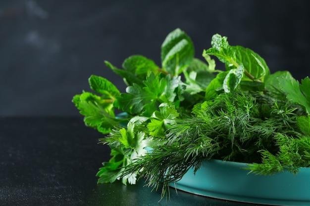 Zielone zioło kulinarne pietruszka, koperek, mięta, bazylia w niebieskim naczyniu