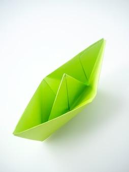 Zielonego papieru łódź kłaść na białym tle.
