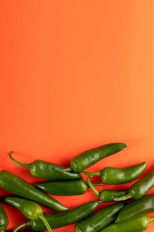 Zielonego pieprzu korzenny świeży na pomarańczowym tle