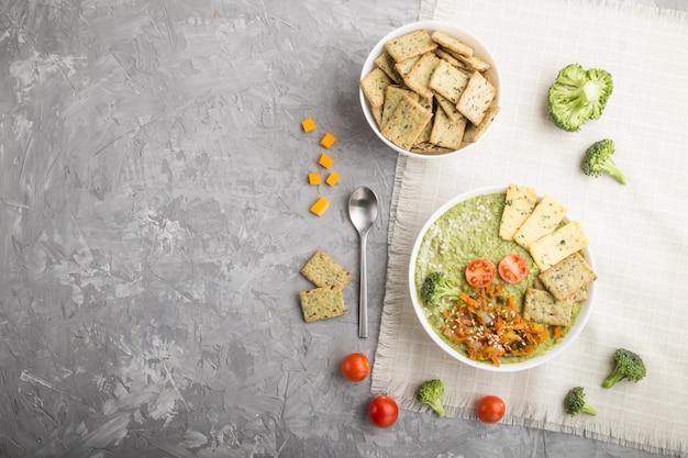 Zielonej brokuły kremowa polewka z krakers w białym pucharze, odgórny widok, copyspace.