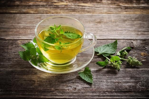 Zielonej melisy ziołowa herbata w szklanej filiżance na drewnianej przestrzeni