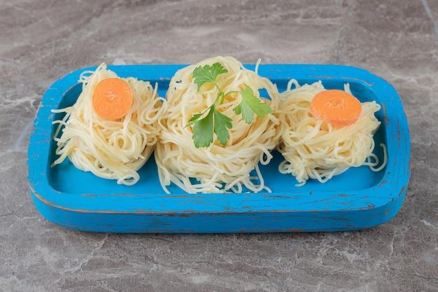 Zieloni i starta marchewka na spaghetti, na drewnianej desce, na marmurowej powierzchni.