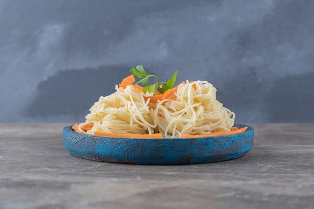 Zieloni i tartą marchewkę na spaghetti, na drewnianej desce, na marmurze.