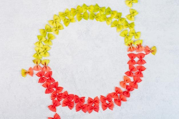 Zielono-czerwony makaron farfalle na marmurowej powierzchni