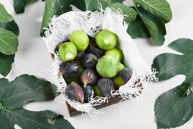 Zielono-fioletowe figi na drewnianej tacy na ręczniku.