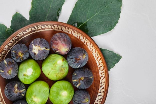 Zielono-fioletowe figi na drewnianym talerzu.