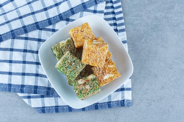 Zielono-żółte tureckie przysmaki w misce na ręczniku, na marmurowym stole.