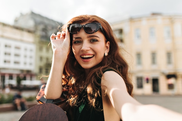 Zielonooka dama zdejmująca okulary przeciwsłoneczne i robiąca selfie