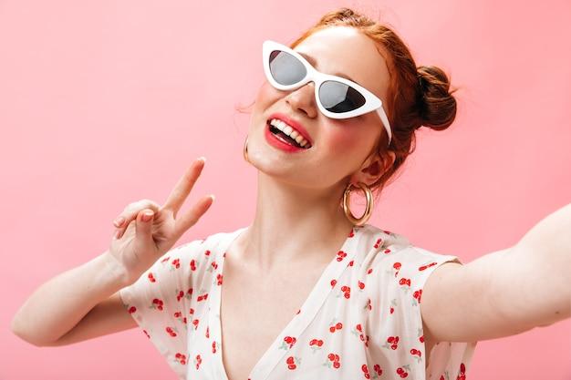 Zielonooka kobieta ze zdumieniem patrzy w kamerę i zdejmuje okulary przeciwsłoneczne.