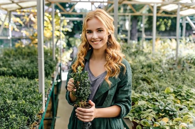 Zielonooka rudowłosa dziewczyna kocha przyrodę. ładny model pozuje z uśmiechem, trzymając roślinę w dłoniach.