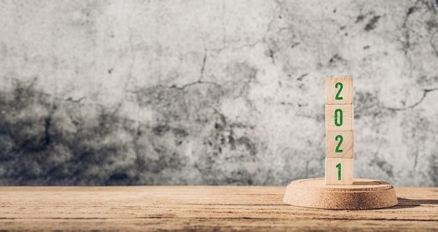 Zielony 2021 na drewnianym stole i betonowej ścianie