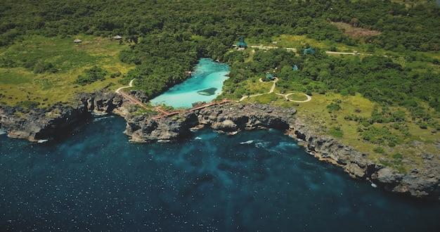Zielony brzeg skały w zatoce oceanu z widokiem z lotu ptaka tropikalnego jeziora słonej wody. nikt nie ma tropikalnej przyrody z turkusową laguną na wybrzeżu weekuri, wyspa sumba, indonezja