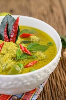 Zielony curry w pucharze na drewnianym stole.
