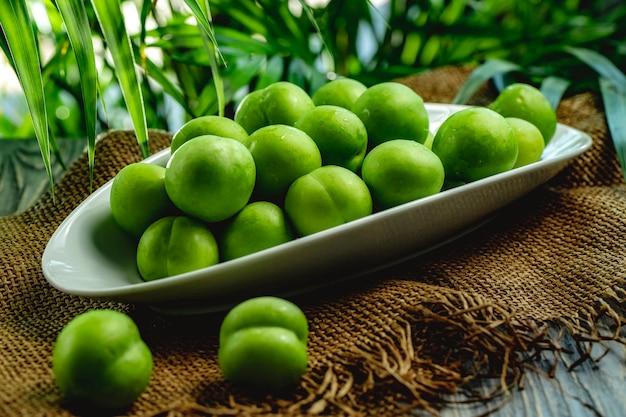 Zielony czereśniowy śliwkowy alycha na białym talerzu