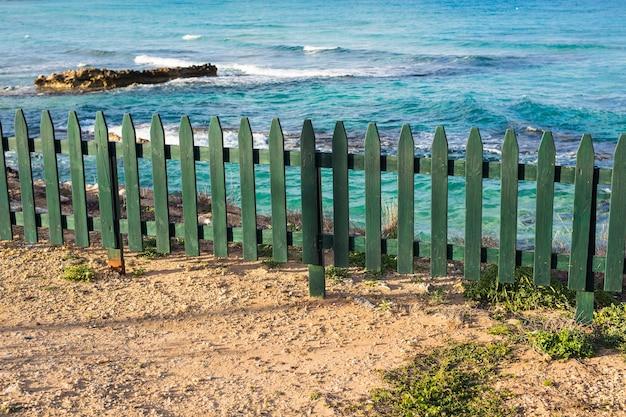 Zielony drewniany mały ozdobny płot na plaży.