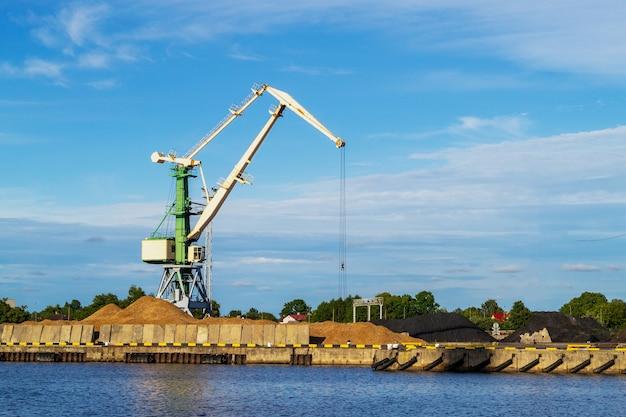 Zielony dźwig towarowy w terminalu w porcie statków rzecznych w ventspils, łotwa, morze bałtyckie. import przesyłek