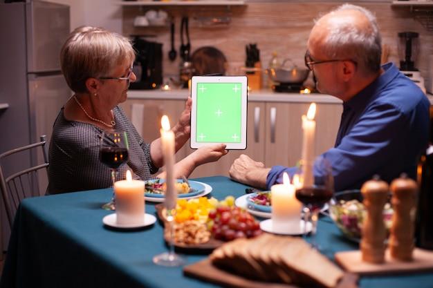 Zielony ekran tabletu na kolację. ludzie w podeszłym wieku patrzący na zielony ekran szablonu chroma key, siedzący przy stole w kuchni podczas kolacji.