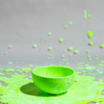 Zielony farby pluśnięcie i filiżanka abstrakta tło