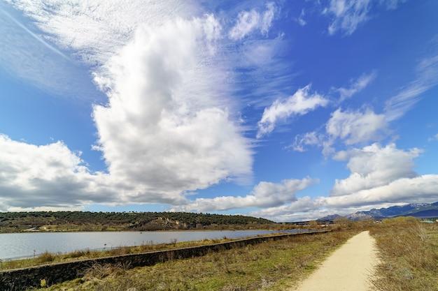 Zielony górski krajobraz z błękitnym jeziorem, polną drogą i dużymi chmurami na niebie, wiosenną atmosferą. guadalix madrid. europa.