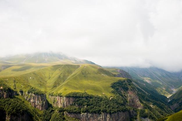 Zielony górski wzgórze doliny krajobraz. góry zbliżają miasto stepantsminda, kazbegi, gruzja.