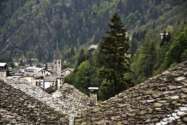 Zielony górzysty krajobraz ze starymi domami na pierwszym planie