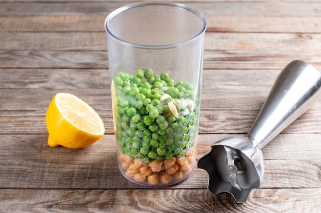 Zielony groszek i ciecierzyca w szklance z blenderem