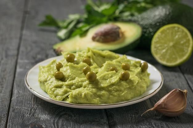 Zielony groszek w misce guacamole na drewnianym stole. dieta wegetariańska meksykańskie jedzenie awokado. surowe jedzenie.
