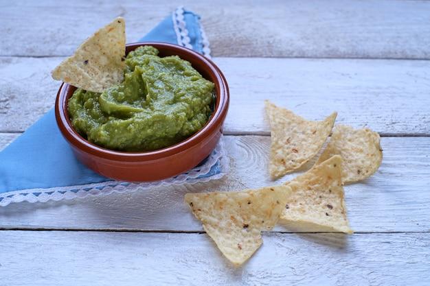 Zielony guacamole z nachos, widok z góry na rustykalny biały drewniany stół. tradycyjne meksykańskie jedzenie.