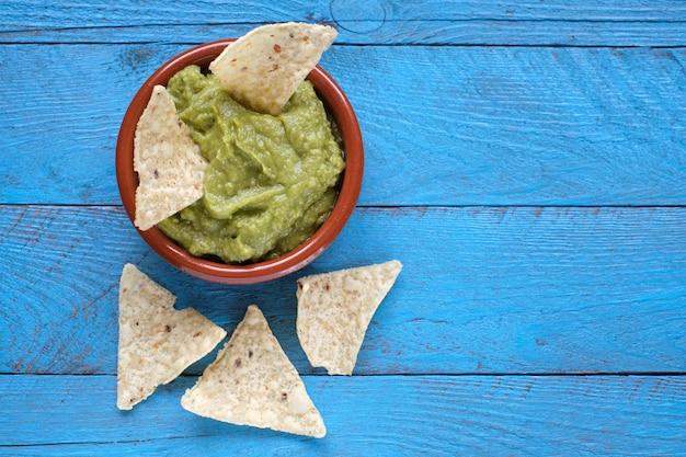 Zielony guacamole z nachos, widok z góry na rustykalny niebieski drewniany stół.