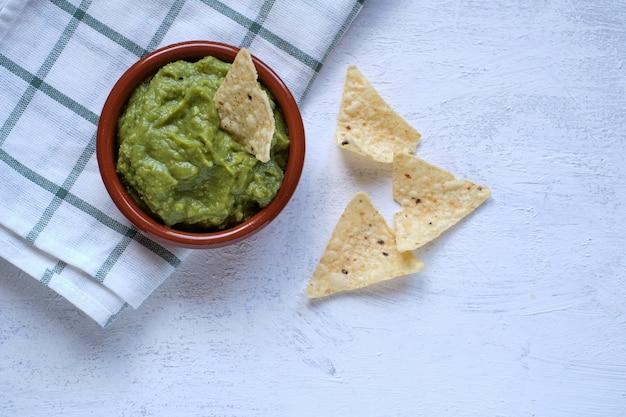 Zielony guacamole z nachos, widok z góry na rustykalnym stole. tradycyjne meksykańskie jedzenie.